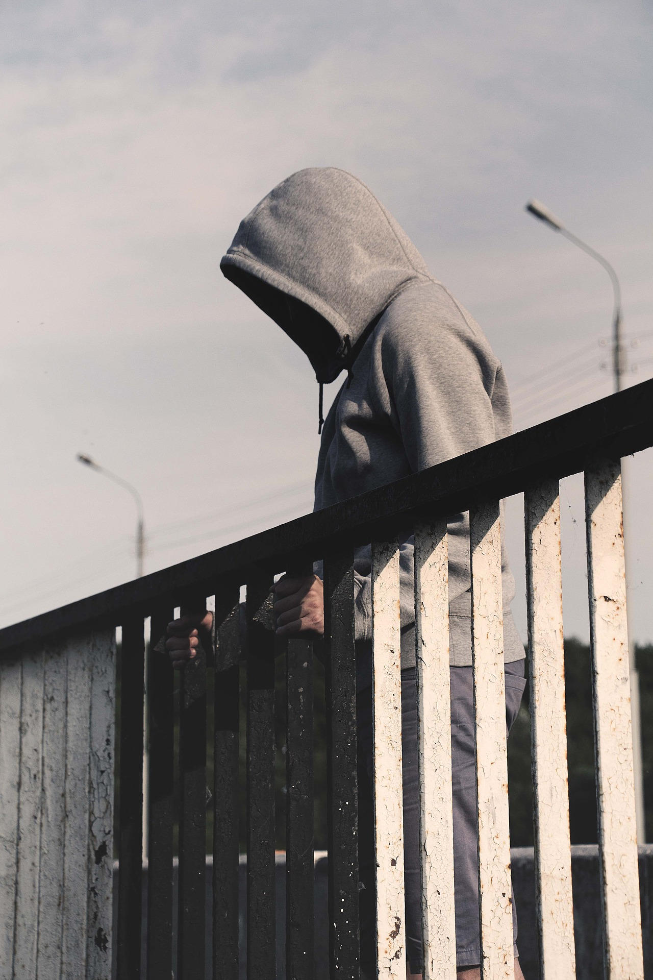 Person in grey hoodie standing on side of bridge with railing